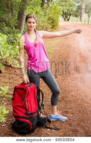 Pretty blonde with backpack hitchhiking in the nature