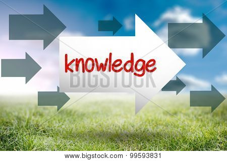 The word knowledge and arrow against sunny landscape