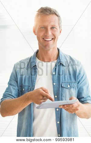 Portrait of a smiling businessman scrolling on a tablet at office