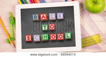 Back to school message against students desk with tablet pc