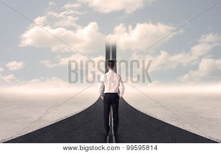 Businessman looking at 3d road that goes up in the sky concept