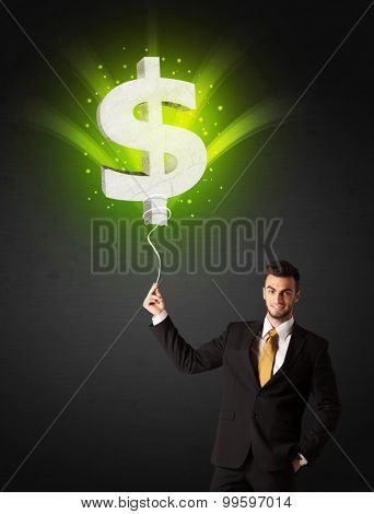 Businessman holding a shining, green dollar sign balloon