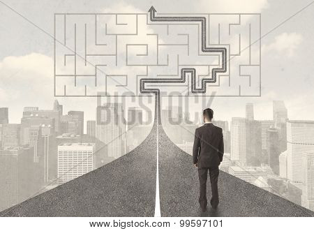 Businessman looking at road with maze and solution concept