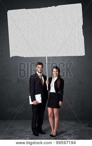 Young business couple holding a big blank booklet paper