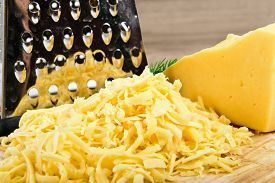 foto of grating  - grated cheese on wooden board - JPG