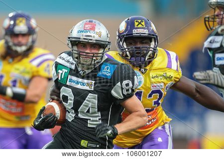 ST. POELTEN, AUSTRIA - JULY 26, 2014: WR Clemens Erlsbacher (#84 Raiders) runs with the ball during Austrian Bowl XXX.