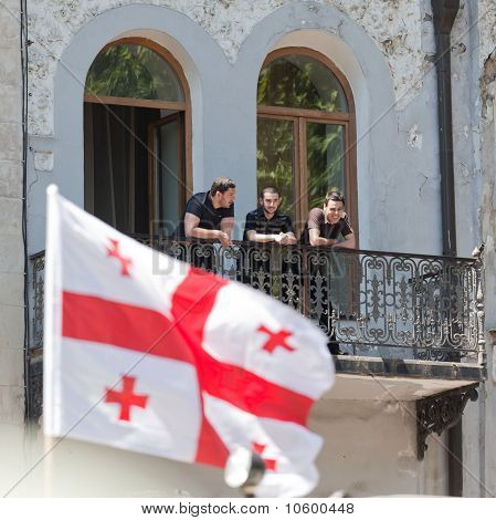 Young Men Watch Military Parade From Balcony. Tbilisi, Georgia.
