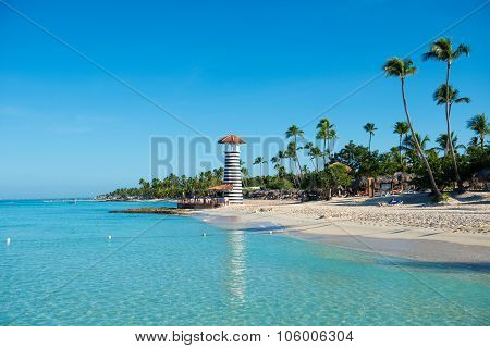 Transparent Sea Water And Clear Sky. Lighthouse On A Sandy Tropical Island With Palm Trees.