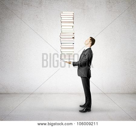 Businessman With A Huge Pile Of Book In A Concrete Room
