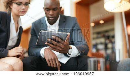 Businesspeople Sitting Together Using Digital Tablet