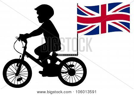 A Kid Silhouette Rides A Bicycle With United Kingdom Flag