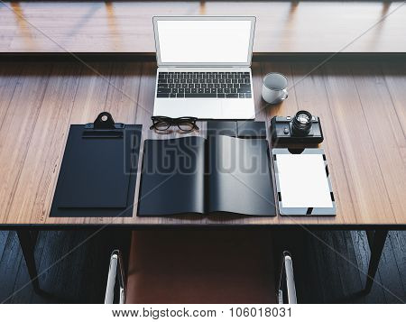 Generic design laptop on the wooden table with office elements. 3D rendering