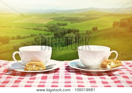 Two coffee cups and cantuccini on the table against Tuscan landscape, Italy