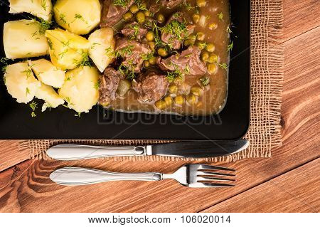 Venison Goulash with potatoes on the black plate.