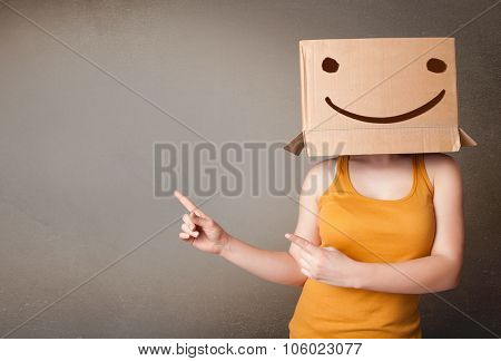 Young lady standing and gesturing with a cardboard box on her head with smiley face