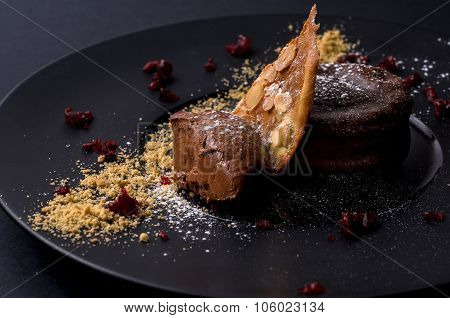 On A Dark Background Chocolate Dessert With Cookies And Nuts