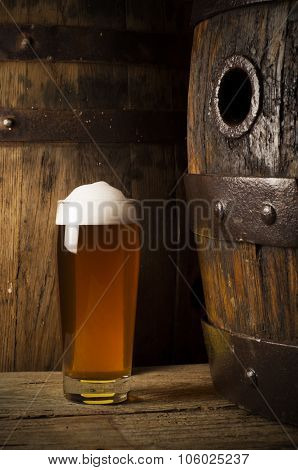 Still life: old wooden barrel of beer, glass of beer and wheat on the table in the cellar.
