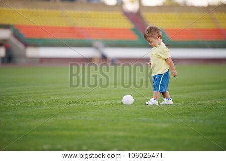 little funny boy on football stadium