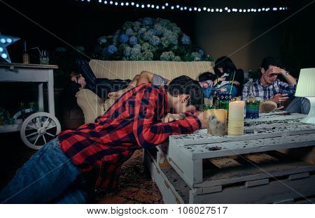 Young drunk and tired friends sleeping after outdoors party