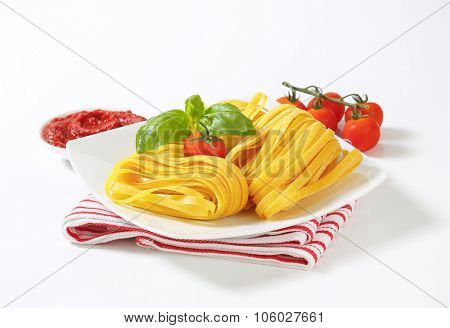 plate of raw fettuccine pasta, cherry tomatoes and tomato sauce on white background