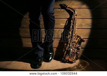 The musician with sax on wooden background, close up