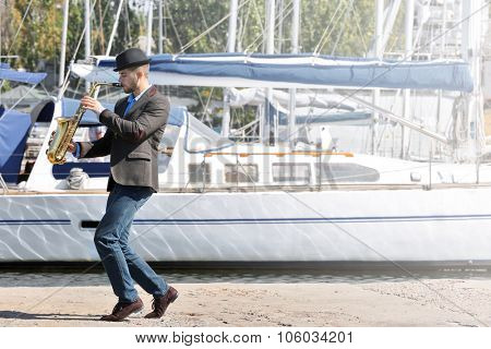 Handsome man plays sax in front of yacht