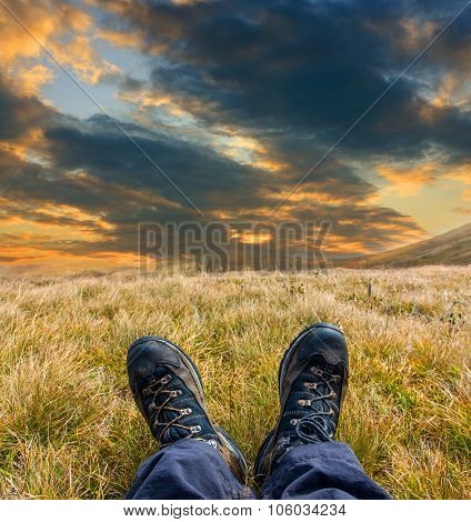 Foots with boots of a hiker on mountain meadow at evening time