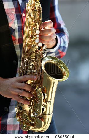 Handsome young man plays sax outdoors, close up