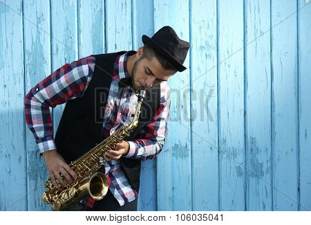 Handsome man in hat plays sax on blue wooden background