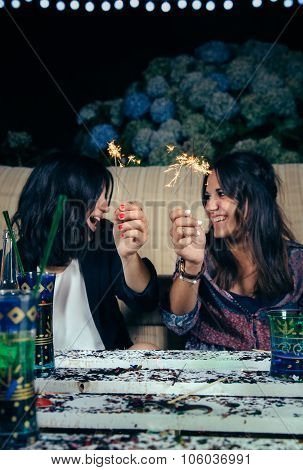 Happy women couple holding sparklers in a party