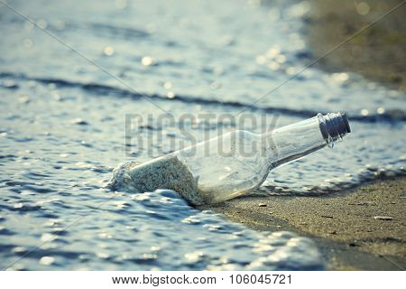 Glass bottle with sand inside on the beach