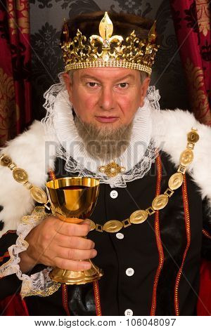 Medieval king toasting with wine in a golden goblet