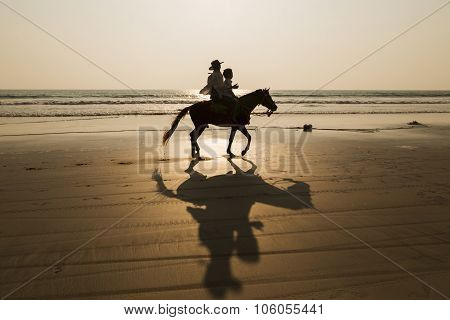Silhouette Man, Boy And Horse On The Beach