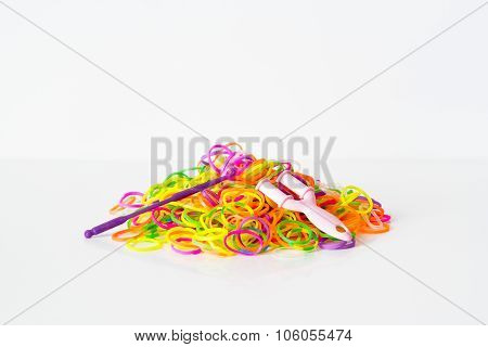 Rainbow loom- Colored rubber bands for weaving accessories on a white background