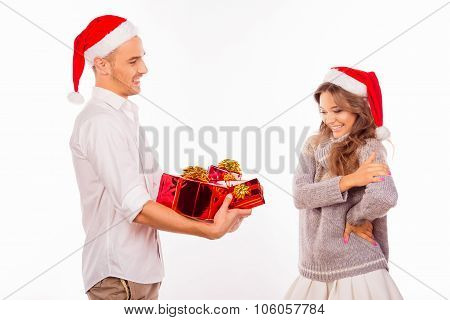 Handsome Young Man Giving A Christmas Presents To His Surprised Girlfriend