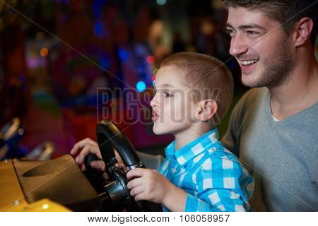 happy father and son playing driving wheel video game in playground theme park