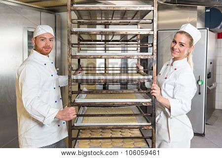 Two Bakers Posing With Shelf Containing Pastry In Bakery