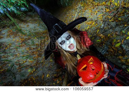 Little Girl Dressed In Witch Costume In Halloween Forest