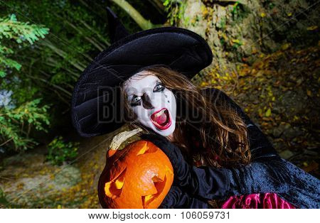 Teenage Girl With Pumpkin In Halloween Forest