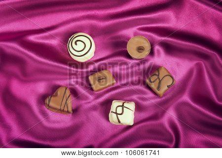 Chocolate candies variety on satin background