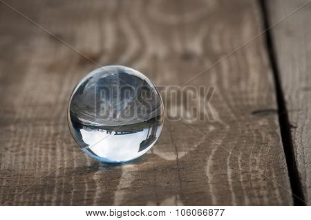 Glass transparent ball on dark background, wooden surface. Soft focus. With empty space for text