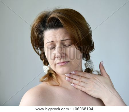 Adult woman with a sore throat on ight background