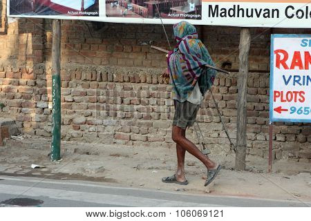 India, Vrindavan. 2013. Hindu hermit walking down the street.