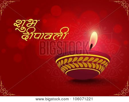 Glossy greeting card with illuminated oil lit lamp and Hindi text Shubh Deepawali (Happy Diwali) for Indian Festival of Lights celebration.