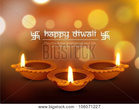 Glossy traditional illuminated oil lit lamps on shiny background for Indian Festival of Lights, Happy Diwali celebration.