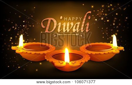 Beautiful traditional illuminated oil lit lamps on shiny brown background for Indian Festival of Lights, Happy Diwali celebration.