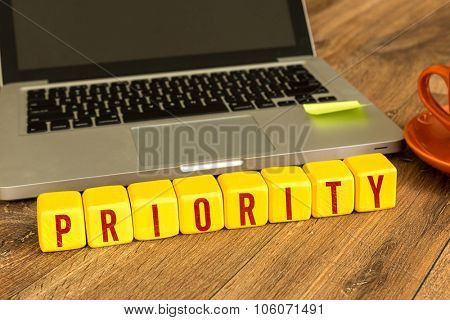 Priority written on a wooden cube in front of a laptop
