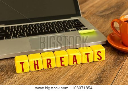Threats written on a wooden cube in front of a laptop