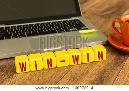 Win-Win written on a wooden cube in front of a laptop