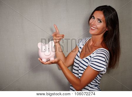 Happy Youngster Pointing A Piggy Bank